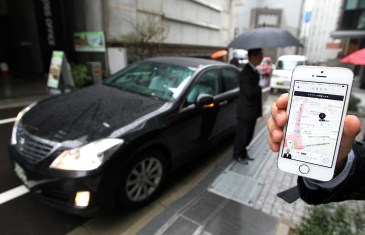 An Uber Japan Co. employee holds an Apple Inc. iPhone 5s showing a map on the Uber application for a photograph during a demonstration in Tokyo, Japan, on Wednesday, March 5, 2014. Uber Technologies Inc., the booking-app developer backed by Google Inc.'s investment arm and Amazon.com Inc. founder Jeff Bezos, expanded to Tokyo using licensed taxi operators rather than private drivers. Photographer: Junko Kimura-Matsumoto/Bloomberg